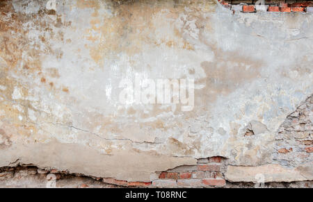 Old grungy red brick wall with peeled beige stucco background. Vintage retro plaster wall with dirty cracked scratched texture background - Stock Photo