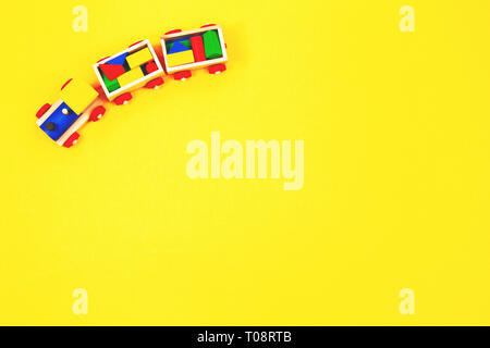 Wooden toy train with colorful blocks on yellow background - Stock Photo