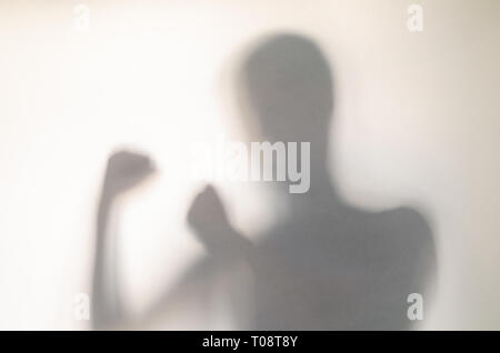 Man in fighting pose behind curtain. Hands and blurry human figure abstraction. - Stock Photo