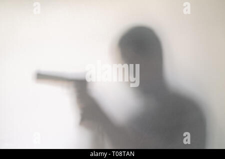 Spooky man behind curtain. Hands and blurry human figure abstraction holding a gun. - Stock Photo