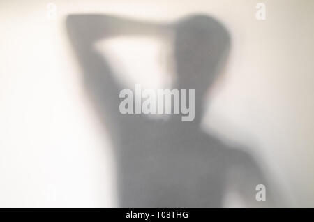 Spooky confused man behind curtain. Blurry human figure abstraction. - Stock Photo
