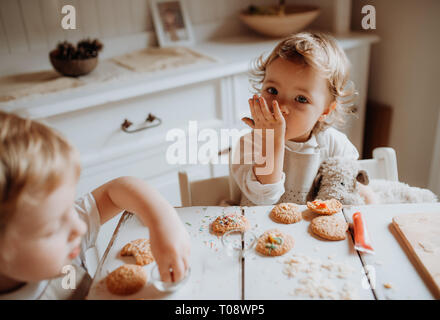 Two small toddler children sitting at the table, decorating and eating cakes at home. - Stock Photo