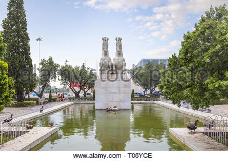 Belem, Lisbon, Portugal - June 23, 2018: Statue of mythical hippocampus jumping over the pond in Empire Square park or Praca do Imperio. - Stock Photo