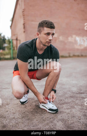 Athlete man crouched, tying shoelaces on sneakers. In the summer on the sports ground in the city. Trainer guy in the watch tracker bracelet after - Stock Photo