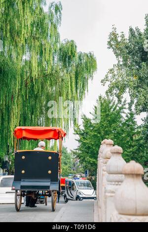 Chinese old traditional rickshaw on Jinding Bridge at Shichahai Qianhai lake in Beijing, China - Stock Photo