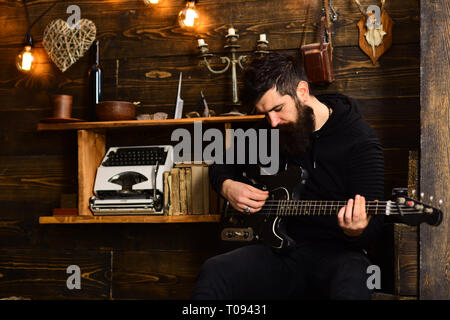 Soul music. Man bearded musician enjoy evening with bass guitar, wooden background. Man with beard holds black electric guitar. Guy in cozy warm - Stock Photo