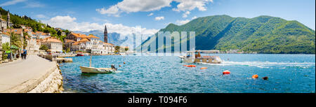 Classic panorama view of the historic town of Perast located at world-famous Bay of Kotor on a beautiful sunny day with blue sky and clouds in summer, - Stock Photo