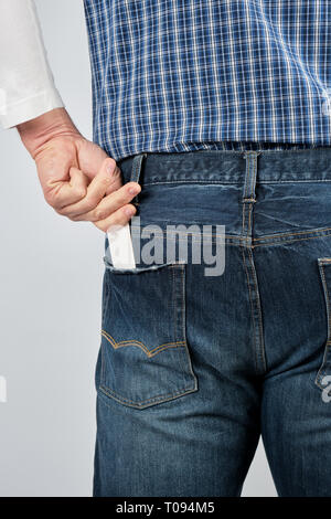 man puts an empty white paper business card in his back jeans pocket, close up - Stock Photo