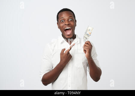 Young rich african american man in shirt holding one hundred dollar with surprise - Stock Photo