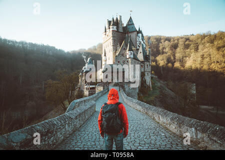 Panorama view of young explorer with backpack taking in the view at famous Eltz Castle at sunrise in fall, Rheinland-Pfalz, Germany - Stock Photo
