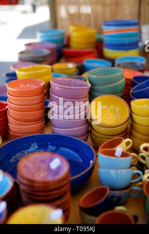 Colourful artisan pottery bowls on a market stall - Stock Photo