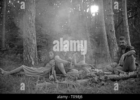 Group of young friends camping in forest. Two couples enjoying picnic on warm summer evening. Tired bearded man cooking food over campfire - Stock Photo