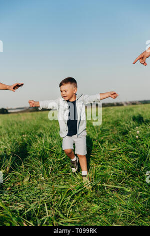 Little boy want to hold hands his parents outdoor. - Stock Photo