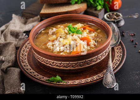 Barley soup with carrots, tomato, celery and meat on a dark background. - Stock Photo