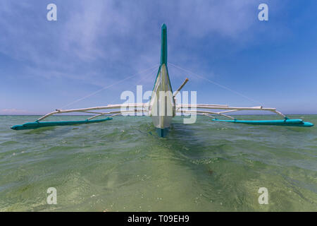 outrigger pumpboat on water in frontview with wide angle lens perspective with a blue sky white clouds background - Stock Photo