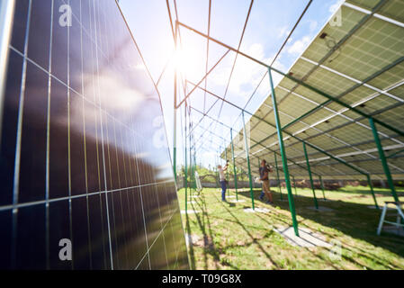 Focus on a solar panel. On blurred background workers mounting innovative solar panels on green metal construction on a sunny day. Providing new techn - Stock Photo