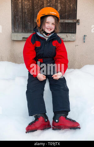 Six-year-old English girl on holiday and wearing ski suit and ski boots but without wearing skis and so not actually skiing. She looks happy. France (104) - Stock Photo