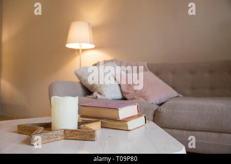 scandinavian interior. brown wall in living cozy room. comfortable room. pink and gray pillows on sofa.Lamp, books and candle on table.Copy space - Stock Photo
