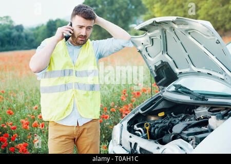Driver in trouble after vehicle breakdown waiting for help - Stock Photo