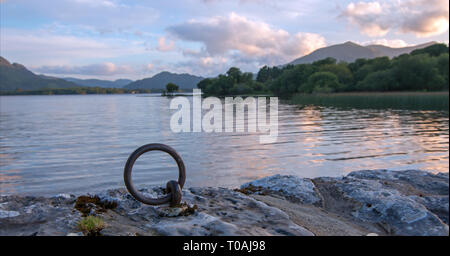 Sunset view of stone boat dock tie up ring of ancient castle ruins McCarthy Mor on Lake Lough Leane at Killarney on the Ring of Kerry in Ireland - Stock Photo