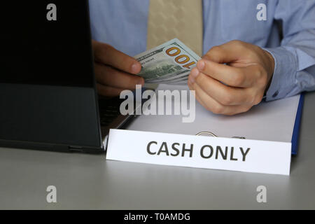 Cash only inscription in office, man in blue shirt and tie holding US dollars in hands. Clerk, official or businessman takes the money, bribe - Stock Photo
