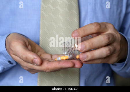 Man with bottle of pills, office employee taking medication in capsules. Concept of antidepressant, stress at work, vitamins, dose of drugs, flu - Stock Photo