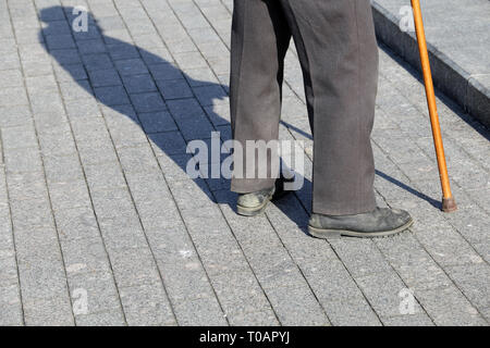Man with walking cane standing on the street near the steps, shadow on pavement. Concept of limping or blind person, disability, old age, poverty - Stock Photo