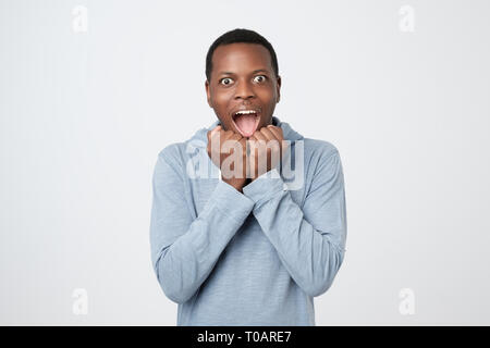 Lucky happy african man as winner clenches fists, rejoices triumph - Stock Photo