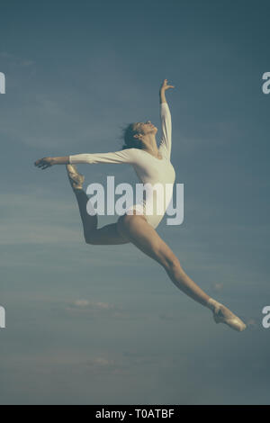 Grace in every move. Practicing art of classical ballet. Ballerina jumping on blue sky. Cute ballet dancer. Pretty woman in dance wear. Ballet class - Stock Photo