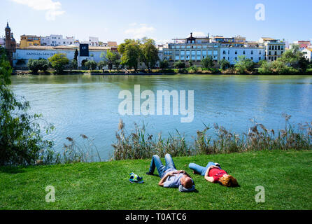 A young couple having a siesta beside the Guadalquivir River in Seville - Stock Photo
