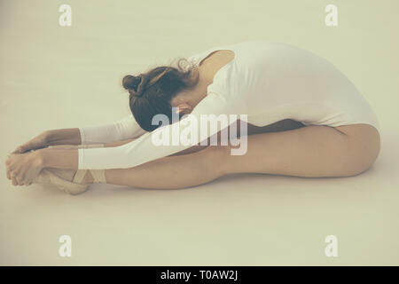 Training her flexibility. Ballet dancer doing stretching exercise. Ballerina in ballet class. Pretty woman in dance wear. Practicing classical ballet - Stock Photo