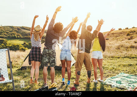 Happy young friends enjoy a sunny day in nature. They're looking at sun and greeting, happy to be together. - Stock Photo
