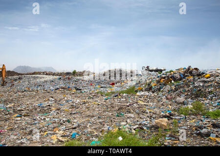 Open landfill area covered with plastic bottles, which ultimately going to burn - Stock Photo