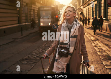 Young beautiful blond woman tourist with a wheeled travel bag and vintage film camera arrives to a new city on a sunny windy evening