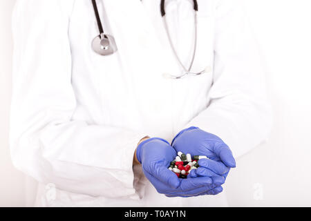 Female doctor hands in medical gloves holding many different pills - Image - Stock Photo