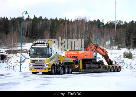 Salo, Finland - March 9, 2019: Yellow Volvo FH16 Mantyla on a yard ready to haul a wide load of Hitachi ZX 350LC tracked excavator on a day of winter. - Stock Photo