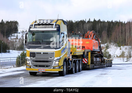 Salo, Finland - March 9, 2019: Volvo FH16 truck Mantyla with low loader trailer carrying Hitachi ZX 350LC excavator as wide load on a day of winter. - Stock Photo