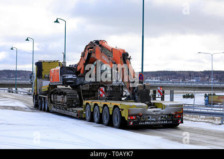 Salo, Finland - March 9, 2019: Volvo FH16 truck with low loader Faymonville trailer carrying a Hitachi ZX 350LC tracked excavator on day of winter. - Stock Photo