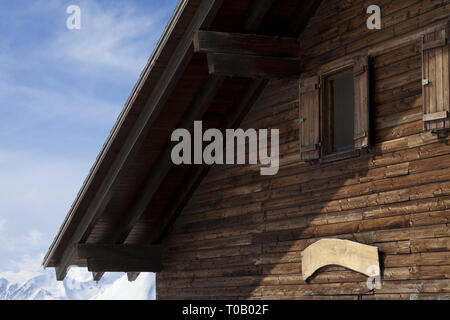 Wall with nameplate and windows of top floor wooden hotel at sunny day in winter mountains. Caucasus Mountains, Georgia, region Gudauri. - Stock Photo