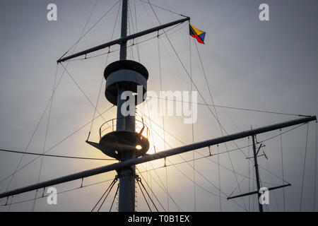 The sun breaking through clouds on the mast of an old sailing ship on Japan's east coast. - Stock Photo