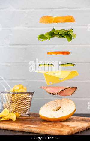 Bagel Sandwich Floating Levitation Falling Ingredients. Fresh and delicious sandwich magical. Rustic white / red brick wall background. Crisps / chips - Stock Photo