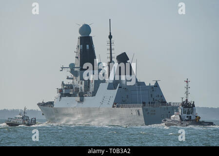 A pilot boat and tug escort the Royal Navy Type 45 destroyer HMS Defender in The Solent, as the warship departs Portsmouth, UK on the 18th March 2019. - Stock Photo