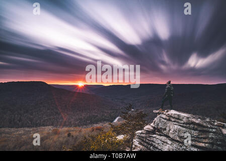 A man stands on the edge of a cliff and stares out over a valley during sunset while clouds captured with a long exposure streak overhead. - Stock Photo