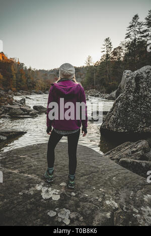 A young woman stands, admiring the river after a hike in a purple Arc'teryx jacket. - Stock Photo