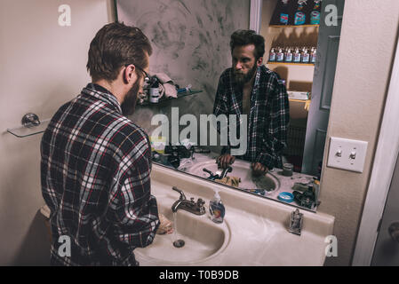 A young man washes his hands in a clean bathroom while his unkempt reflection looks at himself while standing in a dirty bathroom. - Stock Photo