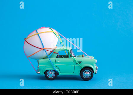 Car toy carrying easter egg tied with colorful thread minimal creative holiday and travel concepts. - Stock Photo