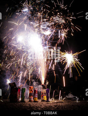 East Brunswick, NJ - July 4, 2017: Consumer grade legal fireworks erupt smoke and sparks; New Jersey legalized sale and use of novelty fireworks and s - Stock Photo