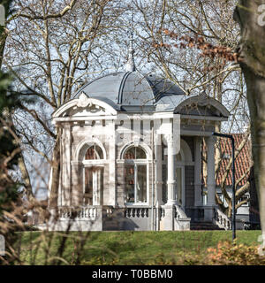 View among the trees of the Tea dome called Gloriette with neoclassical decorations which is located on a hill in the Proosdij park, sunny winter day - Stock Photo