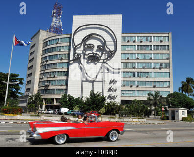 A classic car drives through Havana's Revolution Square, past the Cuban Ministry of Communications building and its sculpture of Camilo Cienfuegos. - Stock Photo