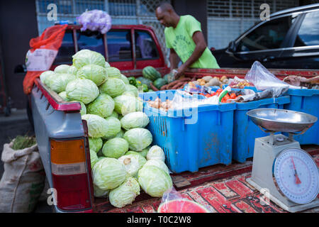 St. Elizabeth / Jamaica - February 2019: A farmer in the background organizes his truck as a make shift shop to sell his produce, St. Elizabeth - Stock Photo